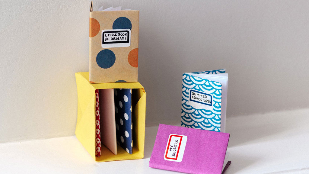 Miniature origami notebooks with patterned and colourful jackets and white pages, on display in a yellow origami bookshelf in a photo for NiMi Projects origami workshops.