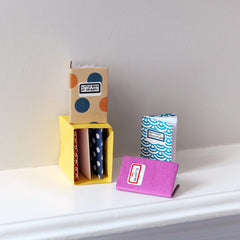 Dotted, pink and blue origami minature notebooks made with dotted paper, displayed around and inside a miniature yellow origami bookshelf in a photo for NiMi Projects Origami Workshops.