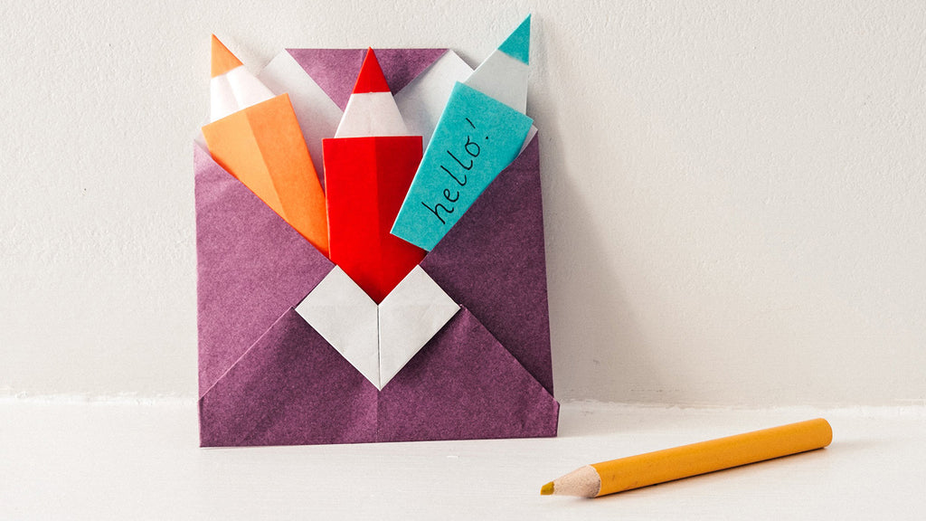 An origami envelope in purple, with a yellow, red and blue pencil shaped notelet set, made for NiMi Projects origami workshops.