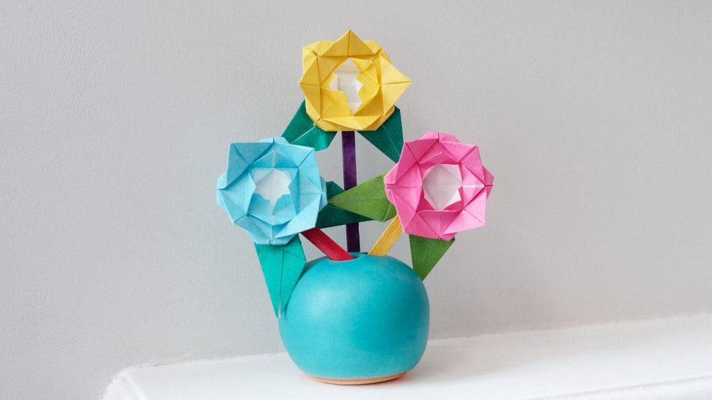 Three origami flowers in blue, yellow and pink, with different colour stems and bright green origami leaves, displayed in an Okada vase handmade in Japan. Photo by NiMi Projects origami workshops.