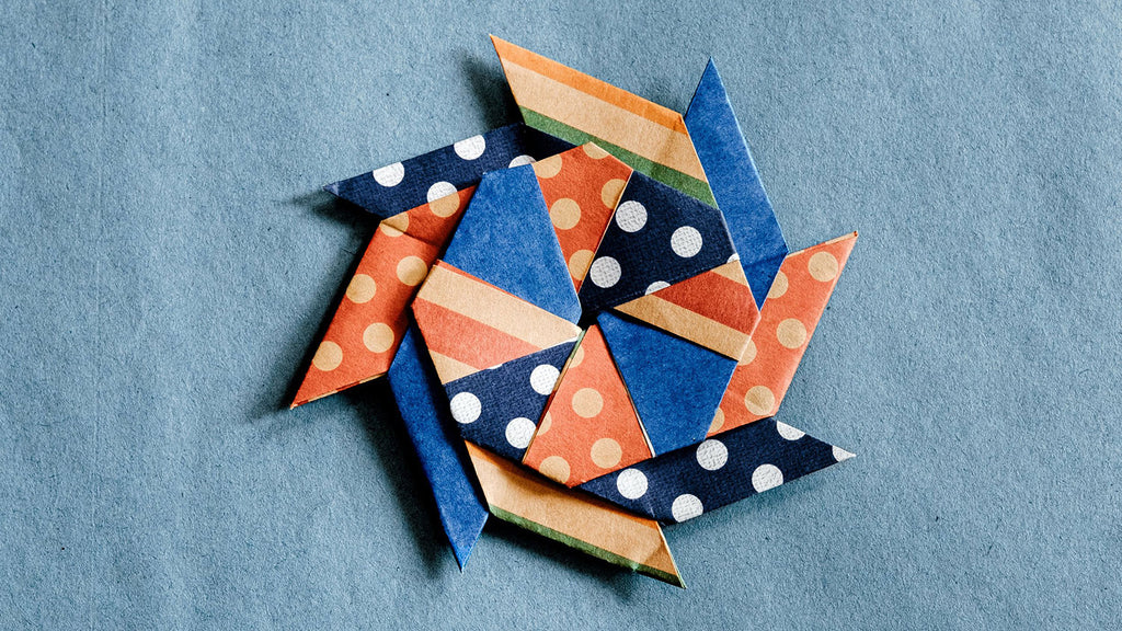 An origami transforming star created from several pieces of striped and dotted paper in blue, red and brown. Photo by NiMi Projects origami workshops.
