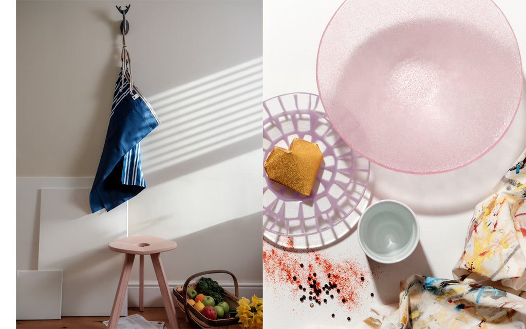 A composite of two images: Left shows a blue and white canvas and cotton Sanpu Sanyo Sanpu apron hanging on a hook above a pink Atelier Yocto three-legged wooden Flower Stool. Right shows two Saburo hand-crafted glass bowls, one with a window pattern, the other frosted. All items are handmade in Japan,  and images shot at NiMi Projects UK.