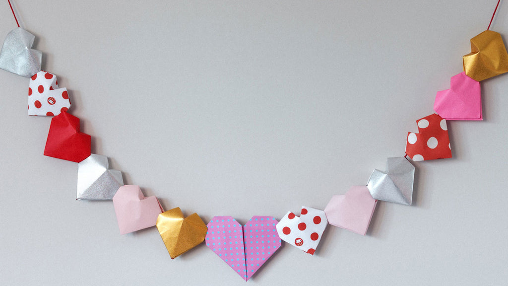 Origami heart hanging bunting in pinks, reds, silver and gold, some patterned with dots, made by NiMi Projects origami workshops.