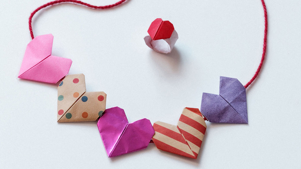 A necklace of five mulitcoloured and patterned origami hearts threaded on red cord, with a matching origami heart ring, made by NiMi Projects origami workshops.