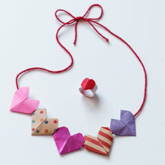 A necklace of origami hearts in pink, multicolored dotted, metalic pink, red striped and purple on a read thread, plus a matching red heart origami ring, made for a NiMi Projects origami workshop.
