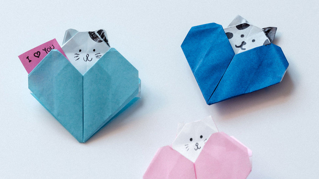 Origami heart envelopes in pale blue, navy blue and pink, each with a little cat head poking out, made for NiMi Projects origami workshops