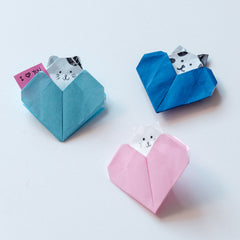 Origami heart notelets in powder blue, bright blue and pink, each with a little cat poking out the top, made for NiMi Projects origami workshops