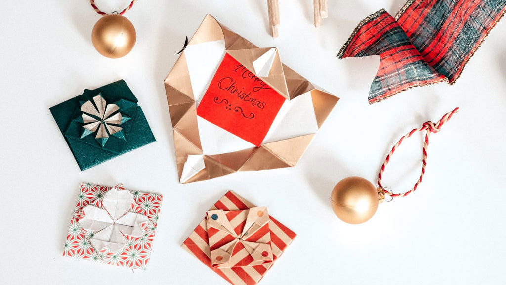 Origami decorative message cards and tiles, each with geometric and floral designs in gold, green and red striped paper. One is folded out to reveal a Christmas message. Photo by NiMi Projects origami workshops.