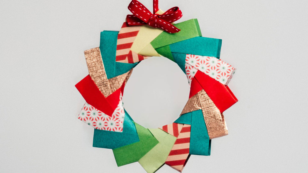 A decorative origami wreath made with multicolored and multi-patterned paper and topped with a red ribbon, made for NiMi Projects origami workshops.
