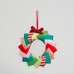 A multicolored and multi-patterned origami wreath, topped with a red ribbon in a photo for NiMi Projects workshops.