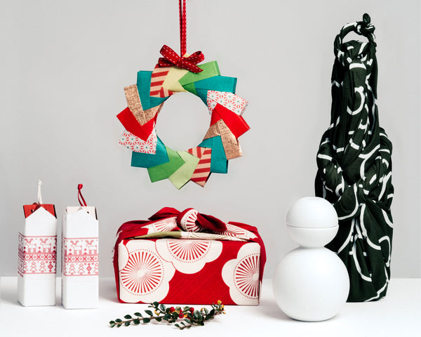 A furoshiki-wrapped gift and bottle, on display at NiMi Projects UK, with two Christmas packaged Sunao Lab House Trivets and a Ceramic Japan Snowman Sake Bottle