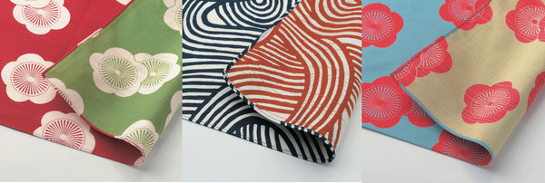 Three reversible furoshiki wrapping cloth patterns: a red and green plum/apricot design, a swirled orange and blue design and a red and blue plum/apricot design
