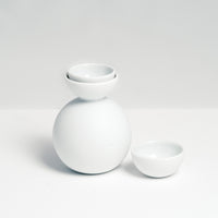 Kaichiro Yamada's white porcelain Snowman Sake set, featuring a rotund sake bottle and two hemisphere cups, one slotted inside the lip of the bottle, the other by its side.  Made in Japan, photographed by NiMi Projects UK