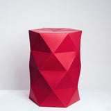 A faceted Catachi 6x4 polygonal paper and cardboard stool in red, inspired by origami folds and designed by Catachi. Made in Japan and available at NiMi Projects UK.
