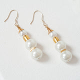 A pair of costume jewellery drop earrings with three pearls, separated by gold parts. Handmade by OMI from recycled vintage jewelry parts sourced in Japan. Sold by NiMi Projects UK.