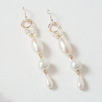 A pair of costume jewellery drop earrings featuring many different sized pearls separated by gold parts. Handmade in Japan by OMI from recycled vintage jewelry parts and deadstock. Sold by NiMi Projects UK.
