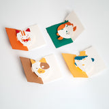 Four Face Popup Cards designed by Yasuyuki Wada for Fukunaga, featuring (clockwise from top left) a cat, girl, dog and boy. Each card comes as a kit of pre-cut colorful paper and has moving eyes and mouth when opened. Made in Japan and available at NiMi Projects UK.