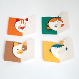 Four Face Popup Cards by Fukunaga, featuring (clockwise from top left) a cat, girl, dog and boy. Each card comes as a kit of pre-cut colorful paper and has moving eyes and mouth when opened.
