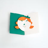 A Face Popup Card, made in Japan and designed by Yasuyuki Wada for Fukunaga, with a green background and a girl's face, complete with orange hair and a green crown.