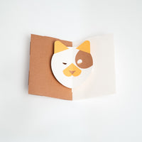 The Dog Face Popup Card, designed by Yasuyuki Wada has a brown background and a white and yellow dog face that moves when the card is opened. This card comes as a DIY kit of pre-cut paper, made in Japan and available in the UK at NiMi Projects.