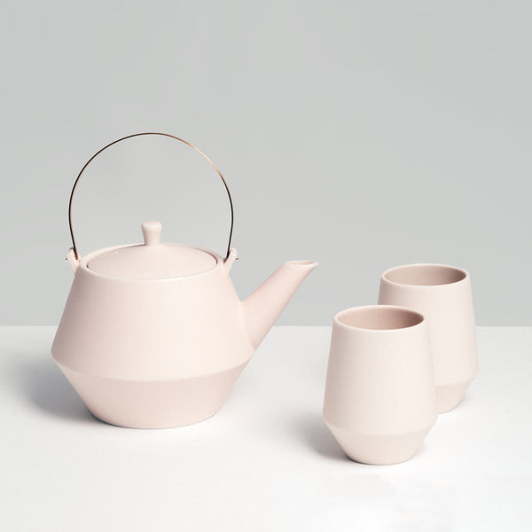Off-white Japanese porcelain Frustum teapot, with brass handle and two matching tea cups, made in Japan and available at NiMi Projects.
