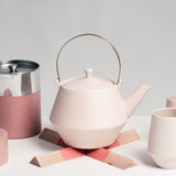 Brass-handled Japanese porcelain Frustum teapot in off white, with matching cups, placed on a pink Sunaolab trivet, available at NiMi Projects in the UK