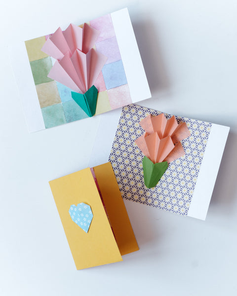 Three origami pop up double layer carnation flower cards, One with a pink concertina petals on a watercolor patterned background, another with coral petals on an asanohana patterned background,  and an orange closed card with a blue origami heart motif on the front. By NiMi Projects origami workshops.