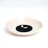 A speckled white Mino ware (Mino-Yaki) porcelain small plate, seen from the side with Trunk Design incense  made in Japan and hand glazed, available at NiMi Projects UK