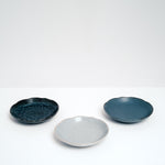 Three Mino-yaki (Minoware) porcelain plates in glossy indigo blue, matte speckled dusty blue and speckled grey. Made in Japan and available at NiMi Projects UK.
