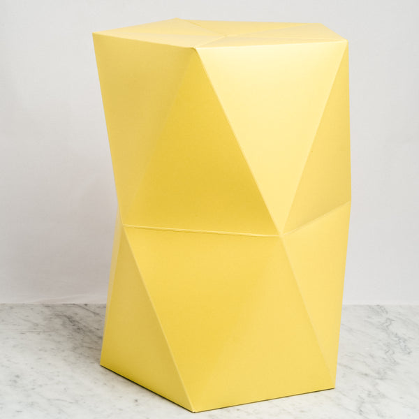 A Catachi yellow origami inspired polygonal stool, constructed in card and paper, and designed and made in Japan. Photographed by NiMi Projects UK.