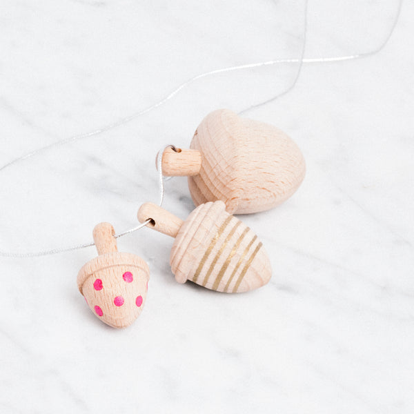 kiko+ & gg wooden spinning acorn necklace doubles as a set of koma spinning tops. Japanese design