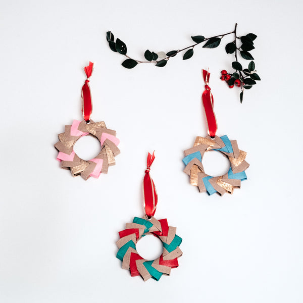 Three origami Christmas wreaths - one in pink, gold and tan, one in blue, gold and tan, and another in red, green and tan - all topped with red ribbon trimmed in gold. Handmade at NiMi Projects UK with Japanese origami paper.