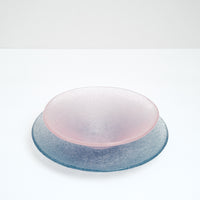 A round blue-purple Shari Shari glass platter paired with a pink Shari Shari conical fruit bowl, both featuring tiny bubbles trapped in the glass for a frosty effect, hand crafted by artisan Saburo in Japan and available at NiMi Projects UK.