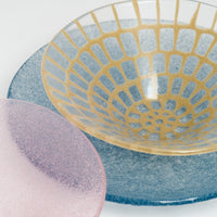 Close up image of Japanese glass artisan Saburo's frosted pink Shari Shari fruit bowl and blue-purple Shari Shari platter, matched with a clear Afumi bowl, featuring a yellow mosaic design.