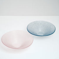 Two large artisanal Shari Shari conical glass bowls — one in pink and the other in blue-purple, made in Japan by Saburo and available at NiMi Projects. The glass features tiny bubbles, giving the bowls a soft frosted effect.
