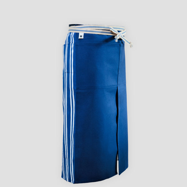 A long Sanpu Sanyo apron in navy blue, as worn, featuring a sailcloth canvas front panel with two pockets and striped pocketed side panels of tenugui cotton. In place of apron strings is a wrap-around sanada himo woven waist cord. Made in Japan and available at NiMi Projects UK.