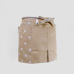 A short beige Sanpu Sanyo apron, as worn, with graphic patterned tenugui cotton pocketed side panels, a sailcloth canvas double-pocketed front and sanada himo woven waist cord. Made in Japan and available at NiMi Projects UK