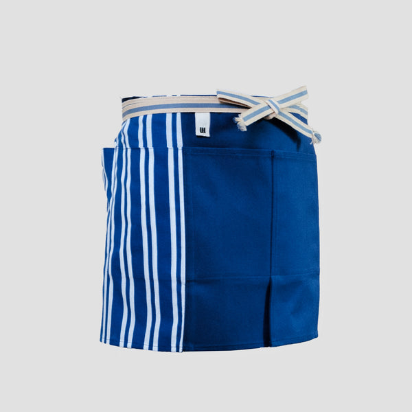 A short Sanpu Sanyo kitchen or gardening apron in navy blue, with sailcloth canvas front panel sporting two pockets, striped side tenugui cotton side panels, and a sanada himo wrap-around  waist cord. Made in Japan and available at NiMi Projects UK.