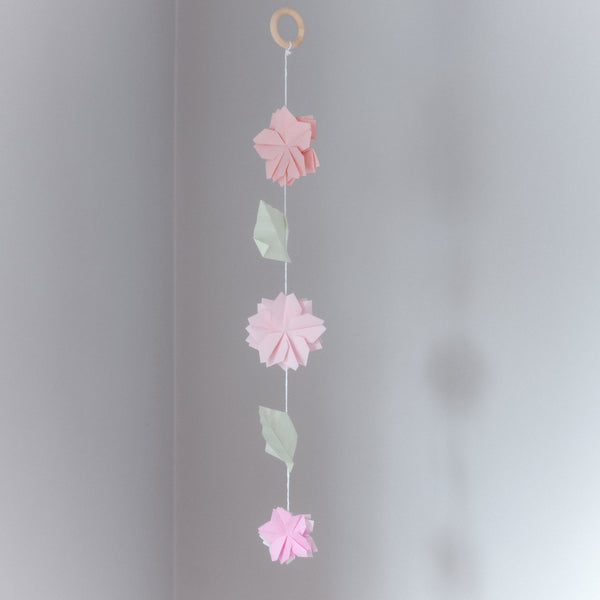 A sakura cherry blossom vertical hanging mobile, featuring three double-petaled paper origami cherry blossom flowers in pink and two origami leaves in pale green - made for NiMi Projects workshops.