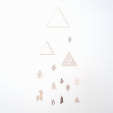 Forest mobile, designed by Sukima and made in Japan, featuring two brass wire triangles, one wood triangle and wooden cutouts of a bird, deer, snowman, stocking and trees. Available at NiMi Projects UK