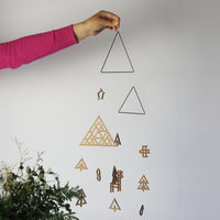 Japanese designer Sukima's wooden Forest mobile, held up to show its size, featuring woodland motifs of a triangular forest, six trees, a deer, a bird, a snowman, a star, a Christmas stocking and two brass triangles.