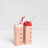 Two standing special-edition SunaoLab house wooden trivets, one with a white roof and red hanging cord, made in Japan and sold at NiMi Projects UK.