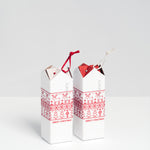 SunaoLab Christmas edition red and white roofed house trivets, wrapped in white cardboard covers decorated with  a cute print of red reindeers and Christmas trees — available at NiMi Projects UK