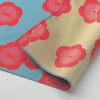 Detail of a reversible cotton furoshiki wrapping cloth with a traditional pattern of apricot blooms in red against a beige background on one side and a sky blue background on the other. Made in Japan and available at NiMi Projects UK