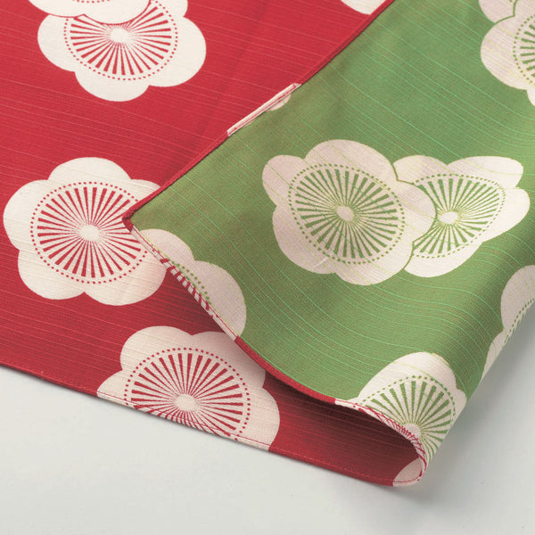 A folded section of a reversible traditional Japanese furoshiki wrapping cloth, decorated with a motif of white apricot flowers on a red background on one side and on a vibrant green background on the other. 100 percent cotton, made in Japan and available at NiMi Projects UK