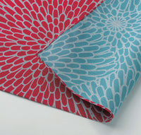 Detail of reversible cotton Japanese furoshiki wrapping cloth, featuring a bold traditional chrysanthemum print in red on one side and in sky blue on the other. Made in Japan and sold at NiMi Projects UK