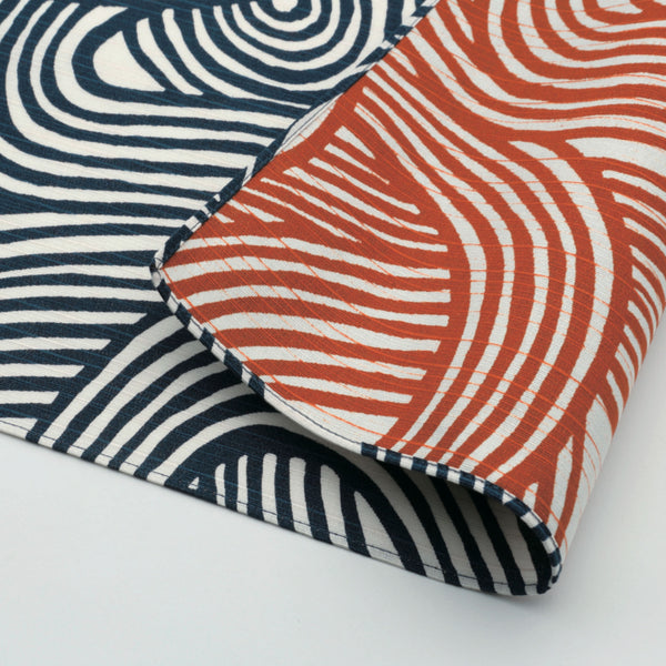 A folded reversible traditional Japanese furoshiki wrapping cloth, featuring a wavy lined knot print in navy blue on one side and in dusty orange on the other. Designed and made in Japan, sold at NiMi Projects UK