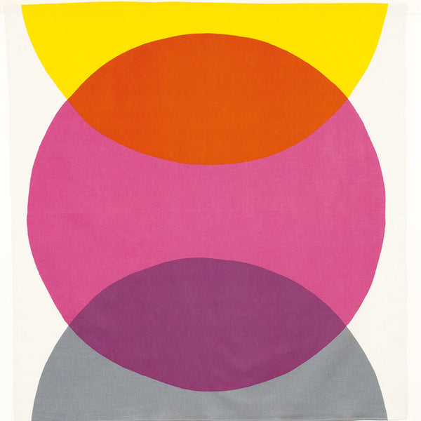 A large Japanese furoshiki wrapping cloth, featuring a geometric design of a large pink circle in the center, overlapped by a yellow semicircle above and a grey semicircle below, made in Japan and available at NiMi Projects.