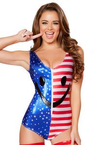 brunnete lady wearing a red white and blue american flag smiley face romper bodysuit and has a finger pointing to her smile