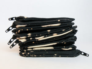 Stack of black zipper pouches with bleach dye pattern
